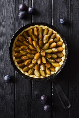 Homemade raw flower shaped plum pie in cast iron pan on black background top view. Low key still life with natural lighting copy space
