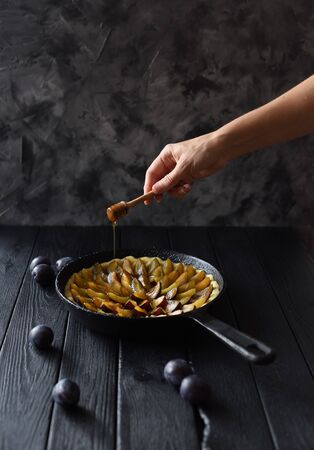 Slender woman hand with honey dipper decorating homemade flower shaped plum pie in cast iron pan on black background copy space