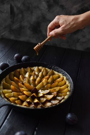 Slender woman hand pouring honey on homemade flower shaped plum pie in cast iron pan on black background copy space