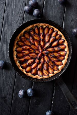 Cooking failure. Burned plum pie in cast iron pan on black background top view. Low key still life with natural lighting copy space