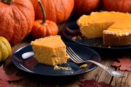 Homemade open pumpkin pie being eaten with orange pumpkins on dark plate rustic style close up
