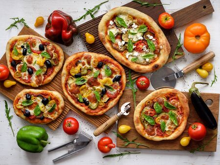 Vegetarian pizza set. Flat lay of homemade big and small pizzas with olives, eggplants, bell peppers, tomatoes and basil served with raw vegetables on white background overhead view
