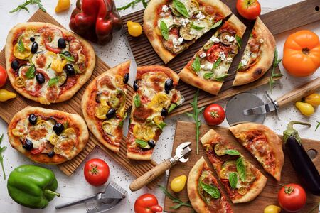 Flat lay of vegetarian pizzas. Freshly made big and small pizzas with eggplants, bell peppers, tomatoes, olives and basil on white background overhead view