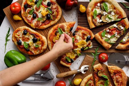 Woman hand putting basil leaves on pizzas. Homemade Italian style pizzas with olives, eggplants, bell peppers, tomatoes and basil on white background top view