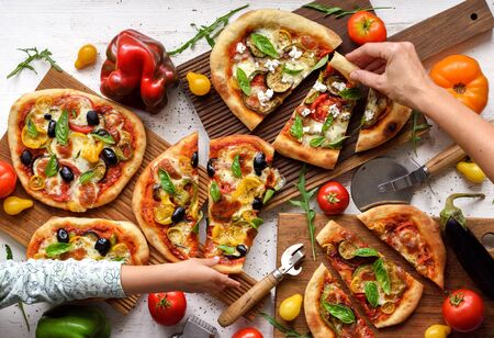 Vegetarian family meal. Woman and child hands reaching for pizza slices with olives and vegetables on white background top view Stock Photo