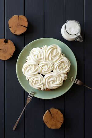 Healthy low sugar cake with coconut cream roses on dark background top view copy space. Still life with natural lighting overhead view