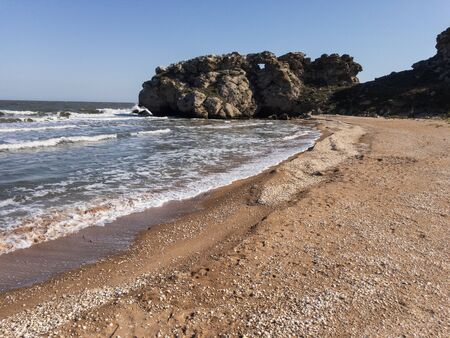 Scenic seascape of Crimea with foamy waves on empty beach, clear blue sky and rocky cliff copy space