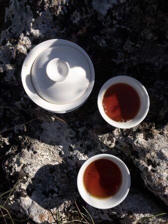Traveling concept. Making black tea in white Chinese gaiwan and cups on big rock top view copy space 写真素材