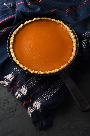 Hygge concept. Homemade pumpkin pie in cast iron pan on dark cozy plaid on black background copy space Reklamní fotografie