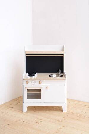 Furniture for children room. White wooden play kitchen with stove, sink and oven in light empty corner copy space