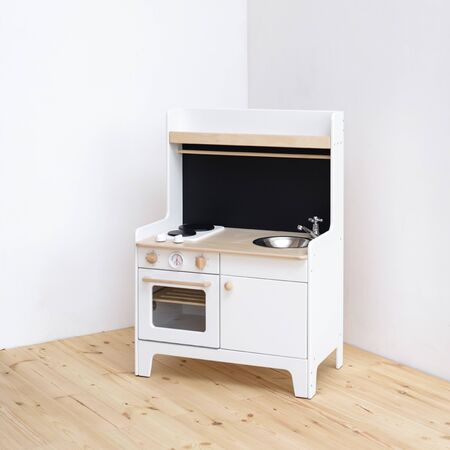 Furniture for children. White play kitchen with stove, sink, black board and oven in light empty corner copy space
