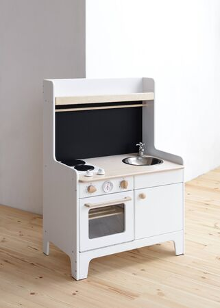 Toy furniture for kids. White wooden play kitchen with stove, sink and oven in light empty room copy space