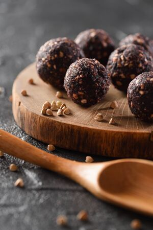 Raw vegan snack. Homemade energy bites made of green buckwheat, nuts and dried fruits on wood slab with wooden spoon on black background Stock fotó