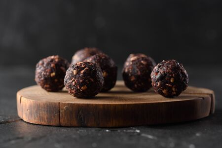 Healthy raw sweets concept. Homemade vegan energy balls with raw buckwheat on wood slab on dark background side view copy space low key natural lighting