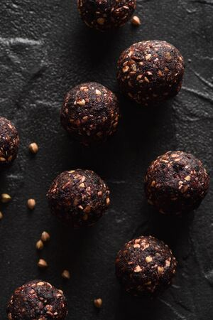 Healthy snack concept. Homemade vegan energy balls with raw buckwheat and dried fruits on black background top view low key natural lighting overhead view