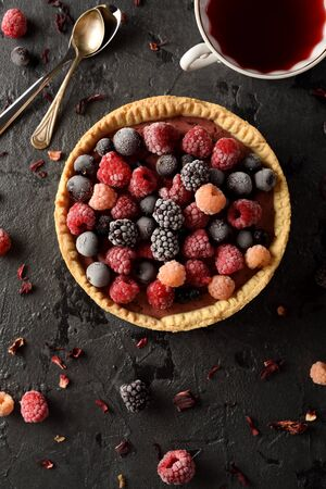 Healthy pastry concept. Delicious open pie with frozen raspberries, blackberries and black currants served with hibiscus tea and dry flowers on black background top view