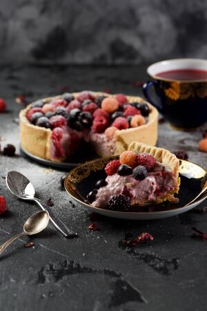Homemade cheesecake with raspberries, blackberries and currants with karkade tea on black background copy space