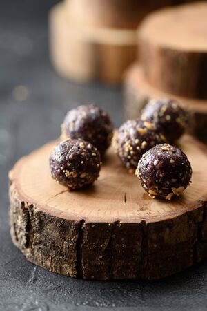 Healthy raw vegan sweets. Homemade energy balls with green buckwheat and nuts on wood slab on black background copy space