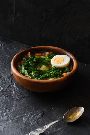 Edible wild herbs concept. Homemade rustic style soup with nettle and egg in wooden bowl with vintage fork on black background angle view copy space