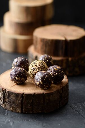 Healthy raw vegan snack. Homemade energy balls on wooden stand on dark background angle view Stock fotó