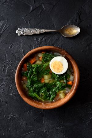 Wild herbs cooking. Rustic style vegetable soup with stinging nettle and boiled egg in wooden bowl with vintage spoon on black background top view copy space