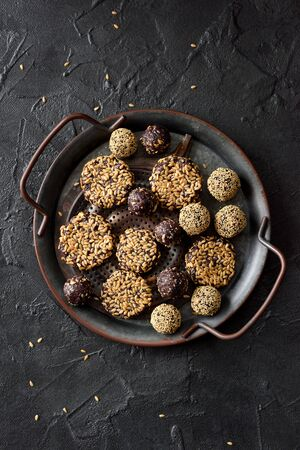 Healthy raw vegan snack. Homemade cookies and balls with flax seeds in metal tray on black background top view copy space.
