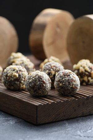 Healthy raw vegan sweets. Homemade energy balls with hazelnuts and wood slabs on dark oak board on black background closeup Stock fotó
