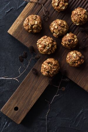 Healthy food concept. Homemade oatmeal bites and dry alder tree branch with cones on oak board on black background top view copy space