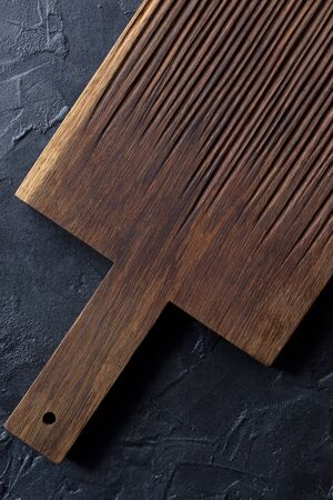 Rustic kitchen utensils concept. Empty dark ribbed oak board on black background top view copy space