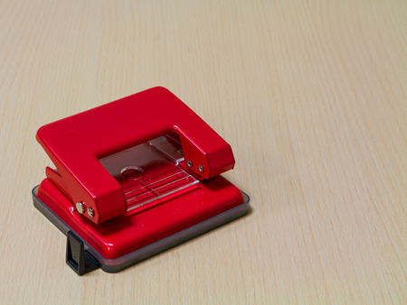 hole puncher: Red  paper hole puncher on wooden background. Stock Photo