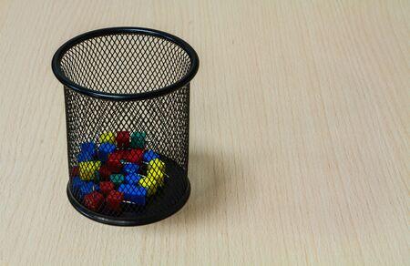 tack: Paper tack in black basket on the wood background.
