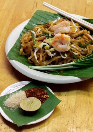 chinese herbs: Thai noodle or padthai with shrimp garnish,vegetable lemon sugar chilli on wood background. Stock Photo