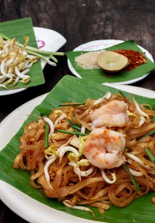 padthai: Thai noodle or padthai with shrimp garnish,vegetable lemon sugar chilli on wood background. Stock Photo