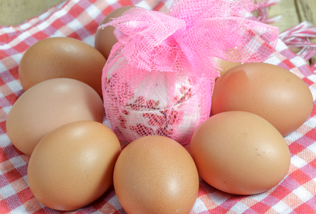 gratuity: The eggs around gift  and cloth on the  wood background. Stock Photo