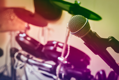 electronic music: Microphone on blur drum background.