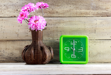 green life: Beautiful pink flower in jar wood ,green clock on wooden background. Stock Photo