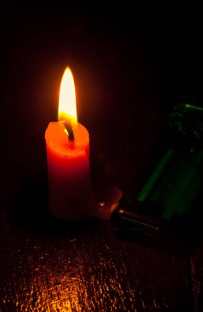 candle flame: candle with green lighter on wood background by dark tone.