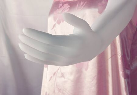 unclothed: hand artificial fitting plastic model on cloth background.