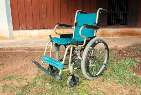 paraplegic: NAKHONRATCHASIMA,THAILAND - NOV 13: Old wheelchair on grass ground on November 13,2015 in Nakhonratchasima,Thailand.