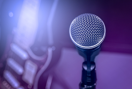 shure: selective focus microphone and blur electric guitar background and flare light.