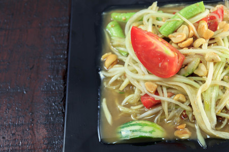 selective focus Thai food the papaya salad or somtum in dish on wood background.