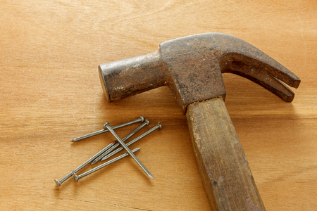 hammer and nails: hammer ,nails on wood background.
