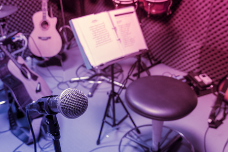 live band: selective focus microphone and blur musical equipment guitar ,lyric, drum piano background.