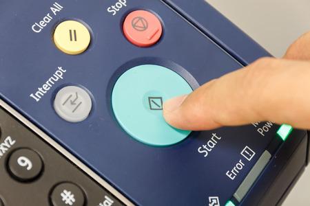 Fingers someone is pushing start copy machine .