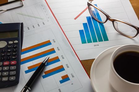 cuadro sinoptico: Resumen de negocios de la pluma enfoque selectivo año, resumen gráfico de la calculadora, café negro, clip de papel en el fondo de madera. Foto de archivo