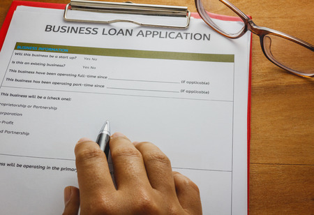 selective focus hand s someone writing on business loan application form by pen.Red paper clip and glasses on wood background.