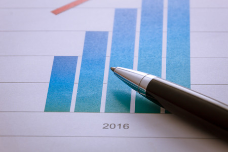 Selective focus pen on  chart in 2016 paper. Stock Photo