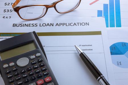 cuadro sinoptico: pluma enfoque selectivo, formulario de solicitud de préstamo de negocios, gráfico, vasos, calculadora, un clip rojo en el fondo de madera. Foto de archivo