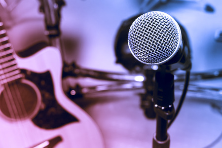 music band: selective focus microphone and blur electric guitar background. Stock Photo