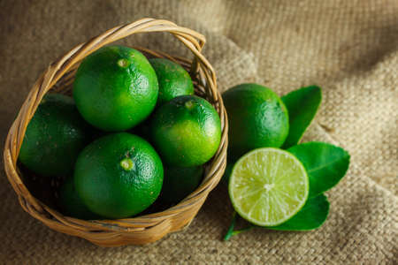 wooden basket: Still life selective focus many lime in the wood basket.Blur to slice  fresh lime and leaf lime on sack background. Stock Photo